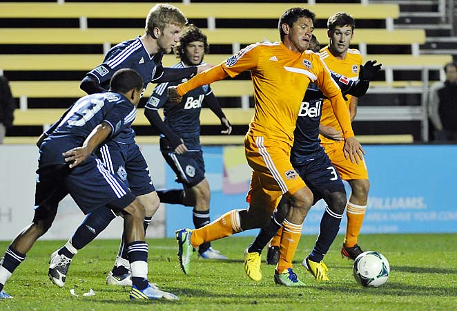 Brian Ching battles for the ball with Whitecaps players during a preseason game.