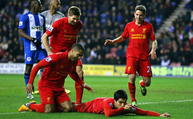 Luis Suarez dives to the ground in celebration after completing his hat trick against Wigan on Saturday.