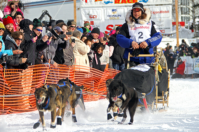 Current Iditarod leader Martin Buser leads his team of dogs back out onto the trail.