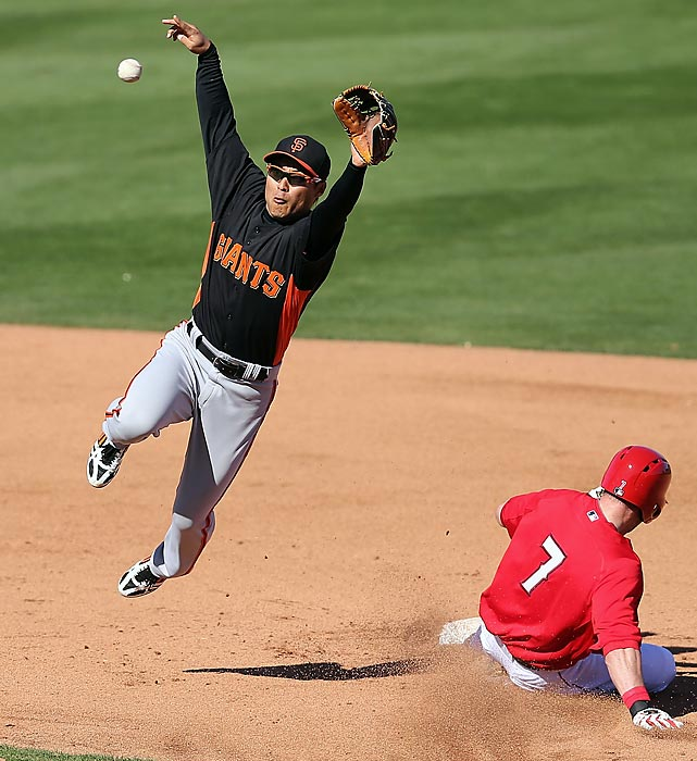 San Francisco Giants infielder Kensuke Tanaka dives from a throw as Los Angeles Angels shortstop Andrew Romine steals second in the fifth inning of a Cactus League game on Feb. 27. Starter Ryan Vogelsong gave the Giants three scoreless innings, but the Angels rallied with two runs in the bottom of the ninth to force an 8-8 tie, the third consecutive draw for the Giants.