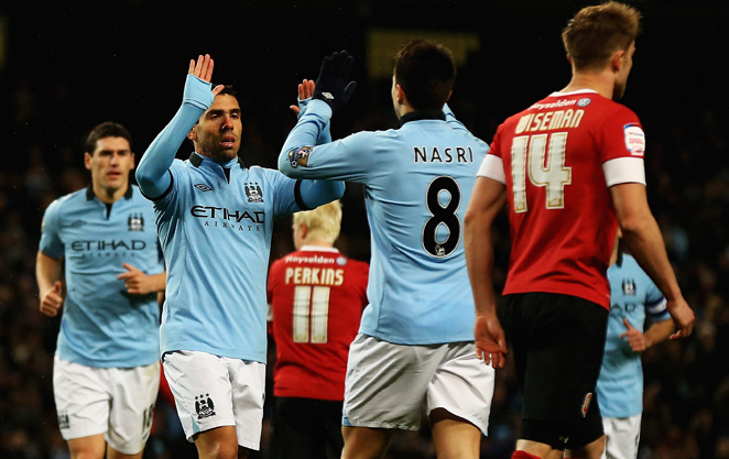Carlos Tevez celebrates with Samir Nasri after one of Tevez's two goals.