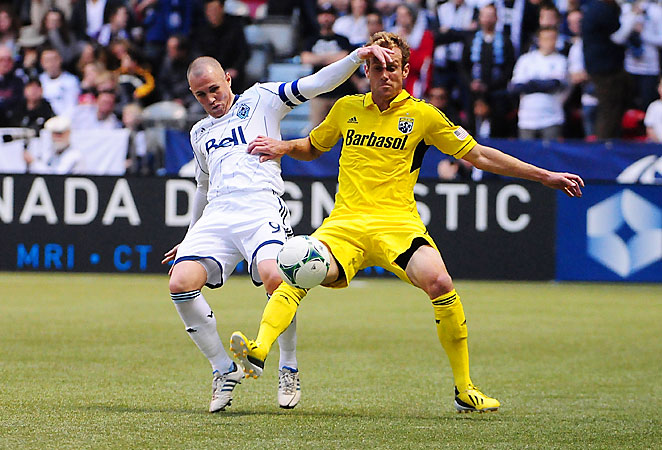 Kenny Miller battles with Tyson Wahl during the Whitecaps' 2-1 win. Miller scored the winning goal in the match.