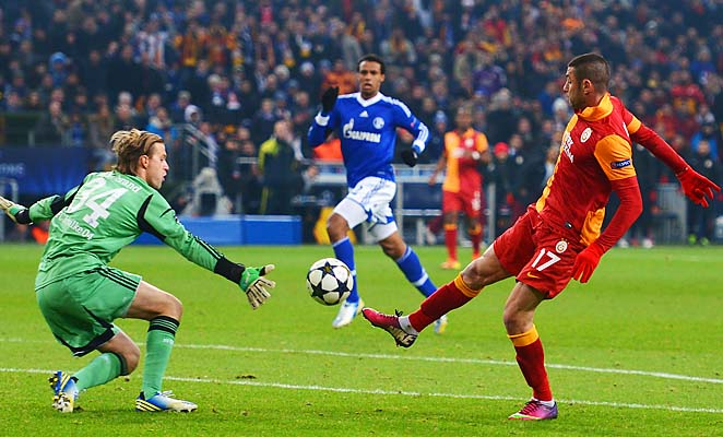 Burak Yilmaz scores in the 42nd minute against Schalke goalie Timo Hildebrand for Galatasaray.
