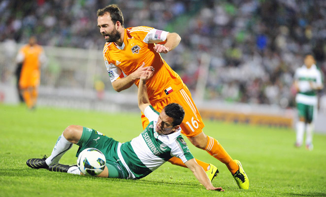 Dynamo midfielder Adam Moffat has the ball taken away with a tackle from Santos Laguna's Juan Pablo Rodriguez Wednesday night.