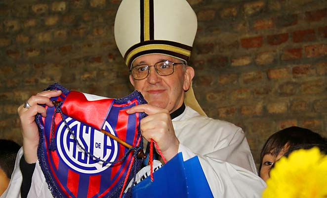 Pope Francis, then Argentine Cardinal Jorge Bergoglio, poses with an emblem from the San Lorenzo soccer club.