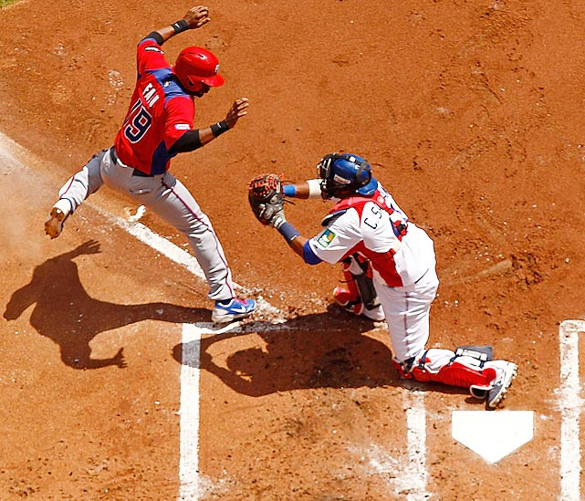 Dominican Republic catcher Carlos Santana tags out Puerto Rico's Irving Falu at the plate during the second round of the World Baseball Classic at Marlins Park in Miami. The play at the plate allowed the Dominican Republic to preserve a shutout in its 2-0 triumph.