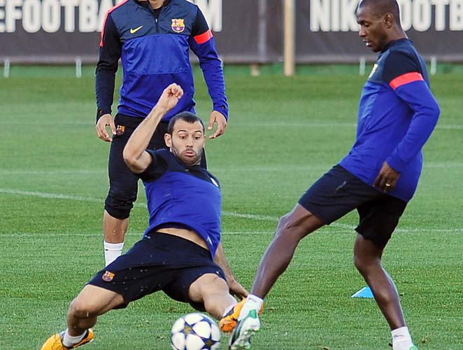 Eric Abidal (right) practices with Barcelona teammate Javier Mascherano.
