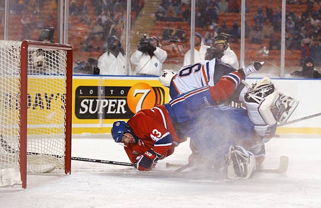 In the main game, the Canadiens prevailed over the Oilers, 4-3. Habs forward Richard Zednik (not pictured, that's Patrice Brisebois taking a tumble courtesy of Ryan Smyth) was credited with scoring the NHL's first open-air goal -- 39 seconds into the second period. It was the first of his two tallies on the night.