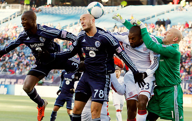 Sporting Kansas City and New England Revolution players collide in the box while going for a cross in their scoreless draw.