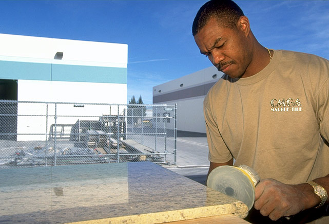 Cunningham sands a slab of marble at his marble tile company in Las Vegas.