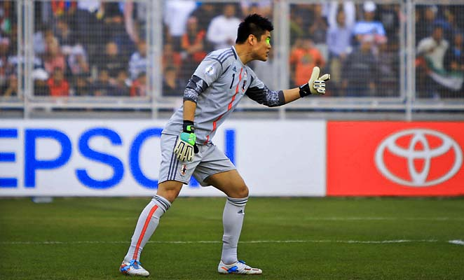 Japan goalkeeper Eiji Kawashima prepares to defend a free kick as a green laser pointer illuminates his face.