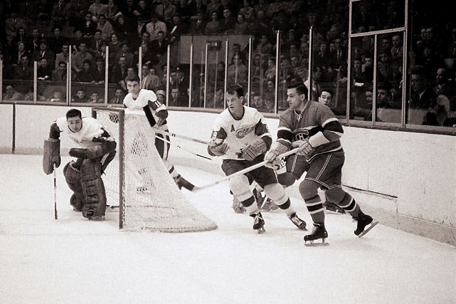 "Howe and the Red Wings battle the Montreal Canadiens in October 1957. He scored 33 goals and 77 points in 64 games that season and won the Hart Memorial Trophy as the NHL's MVP, his fourth of six such honors. His rugged style of play was summed up by the expression ""Gordie Howe hat trick"" -- when a player has a goal, an assist and a fight in the same game."