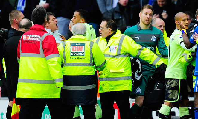 Newcastle United coach John Carver, left in white, yells at Wigan's Callum McManaman at halftime of the Premier League game between the two sides on March 17.
