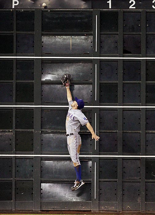 Ian Kinsler leaps at the wall but can't make a catch on a ball hit by Justin Maxwell. It was one of two triples Maxwell had on the night.