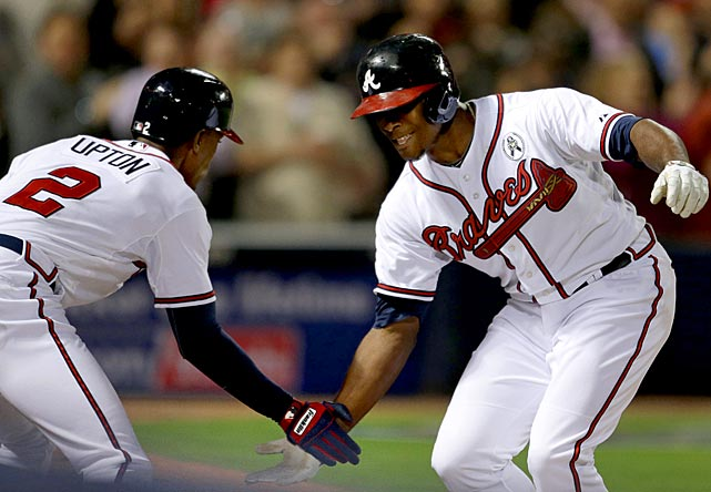 Justin Upton, right, congratulates his brother and teammate B.J. after hitting a home run against the Phillies. Freddie Freeman and Dan Uggla also homered for the Braves.