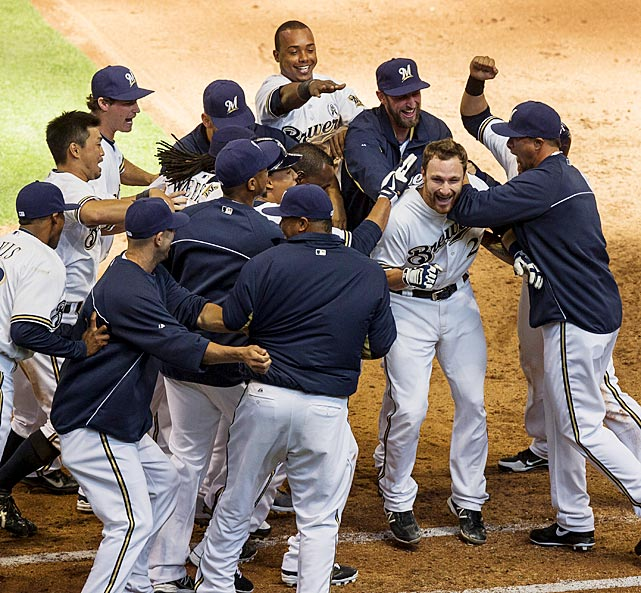 Jonathan Lucroy is swarmed by teammates after his sacrifice fly in the 10th inning gave the Brewers a 5-4 win over the Rockies.