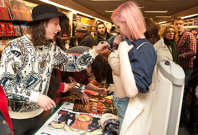An enthalled fan keeps abreast of the Peace axeman's signature scrawl at Head Records in Learningto Spa, England, where the band was promoting the release of its debut album <italics>In Love</italics>.