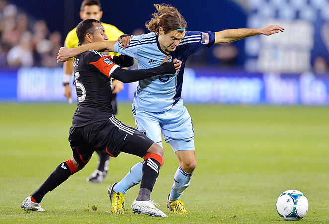 Sporting Kansas City's Graham Zusi battles for the ball with D.C. United's Marcos Sanchez.