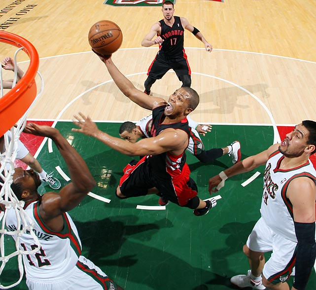 The Raptors' Sebastian Telfair shoots a ball over the Bucks' Luc Richard Mbah a Moute and Gustavo Ayon.