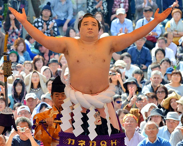 The grand champion is greater than the sumo of his parts as he makes a ritual entrance into the ring at Yasukuni shrine in Tokyo.
