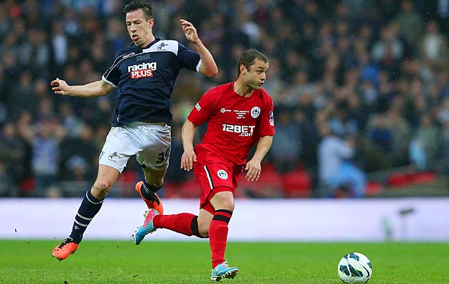 Sean St. Ledger of Millwall and Shaun Maloney of Wigan Athletic vie for the ball.