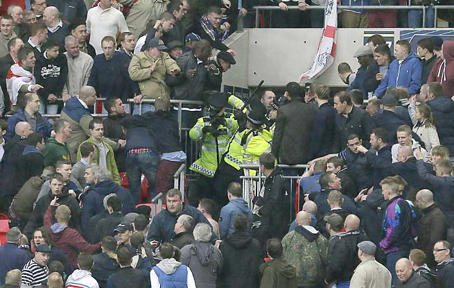 Police officers raise their batons as they control the crowd at the Millwall-Wigan FA Cup semifinal.