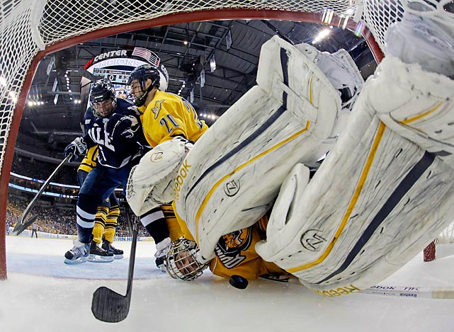 Quinnipiac goalie goalie Eric Hartzell, right, is shoved into the goal cage, dislodging the net, during its 4-0 loss to Yale in the NCAA championship game.