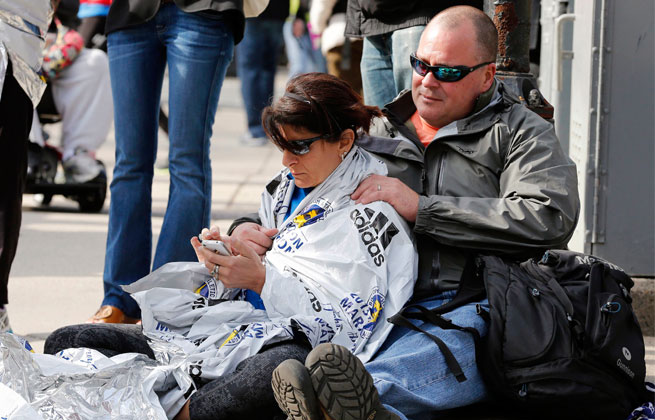 Chris Darmody, right, holds wife Sue. Chris says he was waiting for Sue when an explosion detonated near his location at the finish line of the Boston Marathon. The couple were later reunited after all runners were diverted from the course.