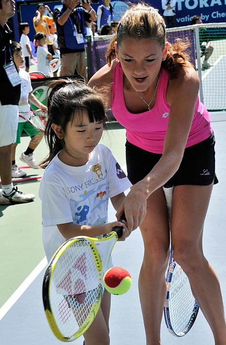 WTA No. 4 Agnieszka Radwanska teaches a young Japanese girl to play tennis at a kids' clinic at the Pan Pacific Open in Tokyo.