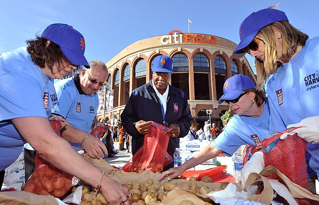 Former Mets outfielder Cleon Jones stands in the center of City Harvest volunteers as he assists in repacking potatoes to help fight hunger.