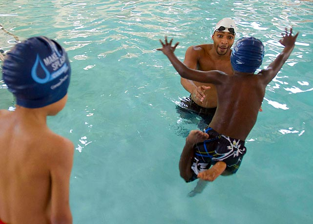 """A child leaps into the pool as Olympic gold medalist swimmer Cullen Jones teaches pre-schoolers the importance of learning to swim during the """"Make a Splash"""" tour in Houston."""
