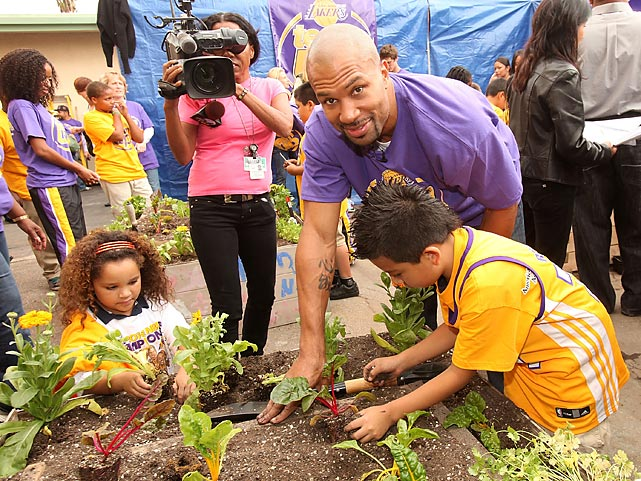 """Former Lakers point guard Derek Fisher helps students at Figueroa Street Elementary School plant a """"Teaching Garden"""" as part of a Meyer and the American Heart Foundation event."""