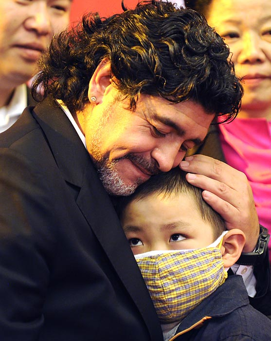 Argentine soccer legend Diego Maradona holds a child cancer patient during a Chinese Red Cross Foundation ceremony in Beijing.