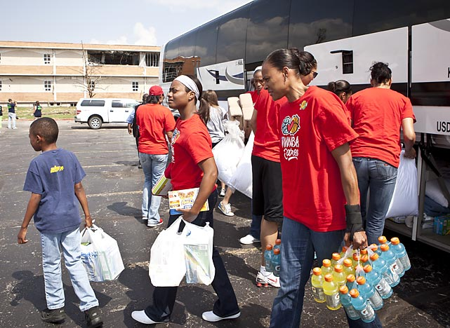 Ivory Latta and Marion Jones, then players with the WNBA's Tulsa Shock, unload supplies from the team bus during a volunteer visit to the site of a tornado in Joplin, Mo.