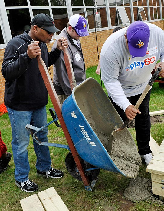 Vikings staff and coaches, including then-assistant coach Mike Singletary (left), help local police, employees and volunteers build a playground at Minnesota's Northport Elementary School.