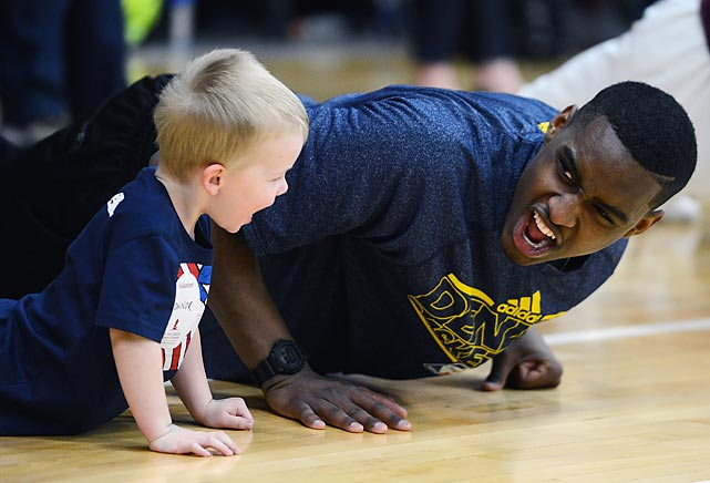 Nuggets rookie Quincy Miller feels the burn as he does push-ups with a young boy during the team's Team Fit Clinic with patients, siblings and supporters from St. Jude's Children's Research Hospital in Denver.