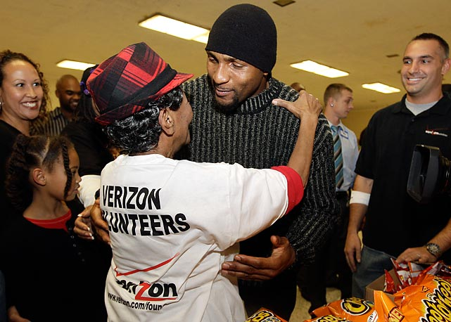 Then-Ravens linebacker Ray Lewis stops to hug volunteer Doris Bailey while distributing Thanksgiving turkeys to families at W.E.B. DuBois High School in Baltimore.