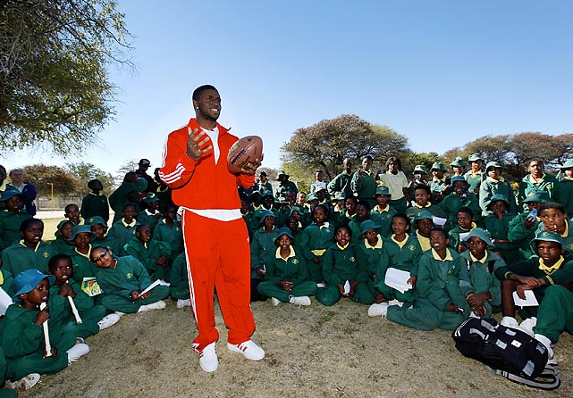 NFL running back Reggie Bush takes the game beyond borders as he teaches school children from Acacia Primary School to throw a football during a visit to Botswana.