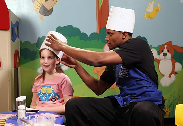 Then-Grizzlies forward Rudy Gay helps a young girl adjust her hat while they decorate cookies during a visit to the Memphis Grizzlies House at St. Jude Children's Research Hospital in Memphis.