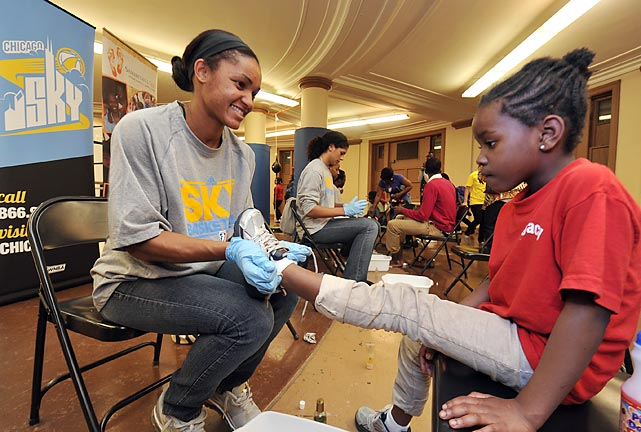 Sydney Carter of the WNBA's Sky fits a young girl with a new pair of shoes as part of the Samaritan Feet Shoe Distribution in Chicago.