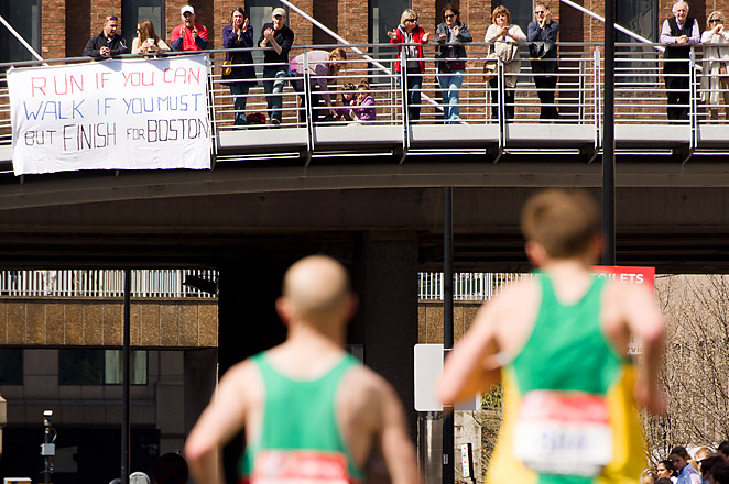 Crowds at Sunday's London Marathon paid tribute to Boston with signs and a moment of silence.