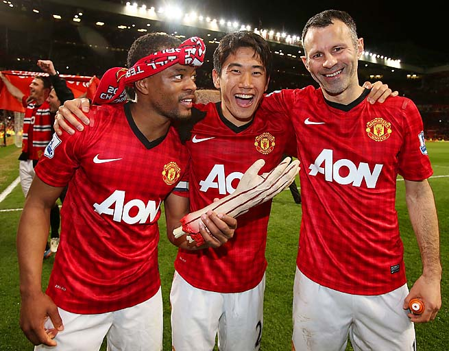 Patrice Evra (left) celebrates with a fake arm, Shinji Kagawa and Ryan Giggs.
