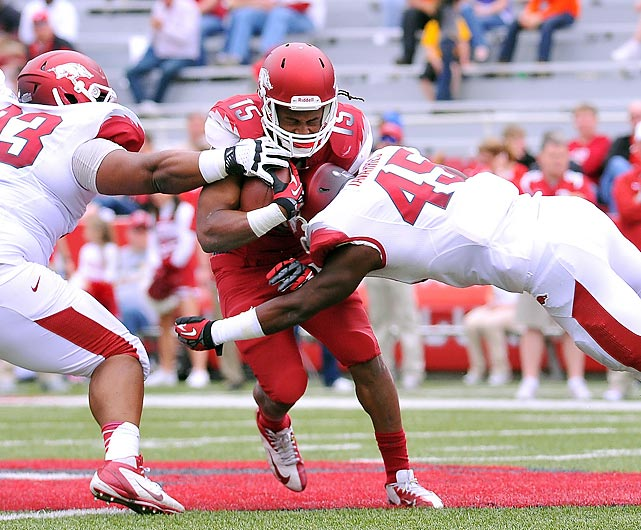 Myke Tavarres (45) and DeMarcus Hodge (93) team up on running back Keante Minor in Arkansas' spring game. Minor and the Red team came out on top, defeating the White 34-27.