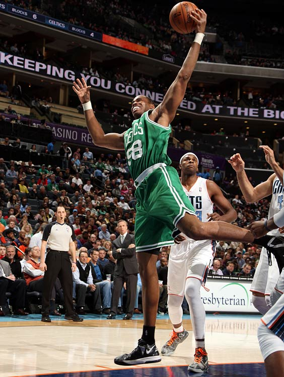 Jason Collins, playing with the Celtics, brings down a rebound against the Bobcats' Brendan Haywood in 2013.