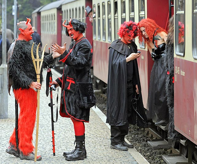 Here we have what appear to be two New Jersey Devils fans, obviously disheartened by their team's failure to make the playoffs this year, preparing to board a train with their spouses in Schierke, Germany, during a traditional religious holiday of pre-Christian origins.