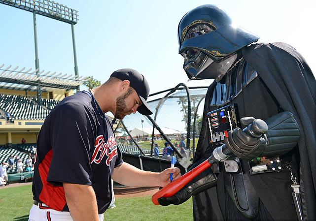 Braves catcher Evan Gattis autographs a lightsaber bat for Darth Vader before a spring training game at Champion Stadium at ESPN Wide World of Sports Complex on March 15, 2013 in Lake Buena Vista, Fla.