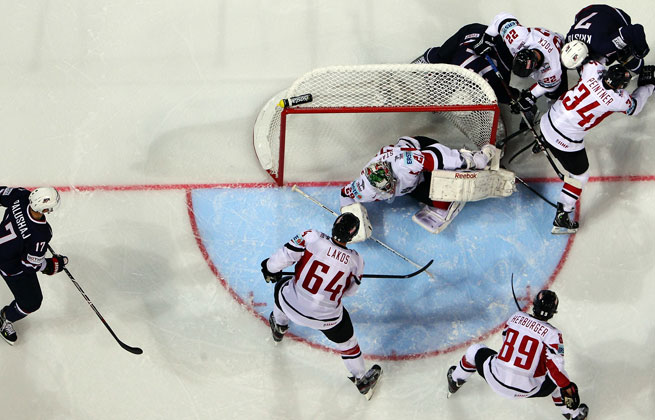 The U.S. (in blue) rallied from down 2-0 to beat Austria 5-3 in its opening game at the ice hockey world championship.