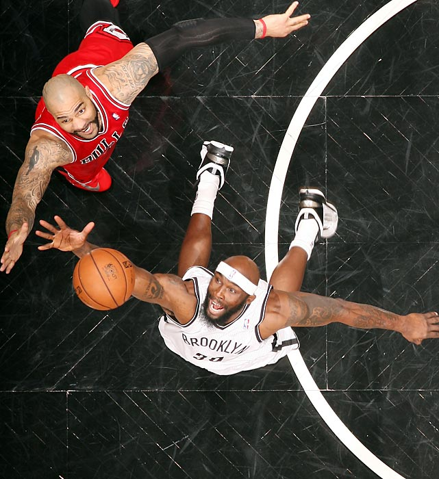 Reggie Evans of the Brooklyn Nets and Carlos Boozer of the Chicago Bulls stretch for a rebound as the Bulls clinched the quarterfinal series with a 99-93 win on May 4.