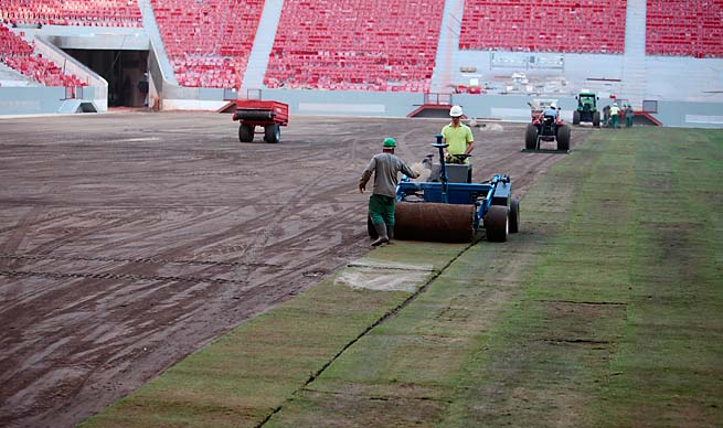 Employees roll out lawn turf at the National Stadium in Brasilia, a Confederations Cup stadium.
