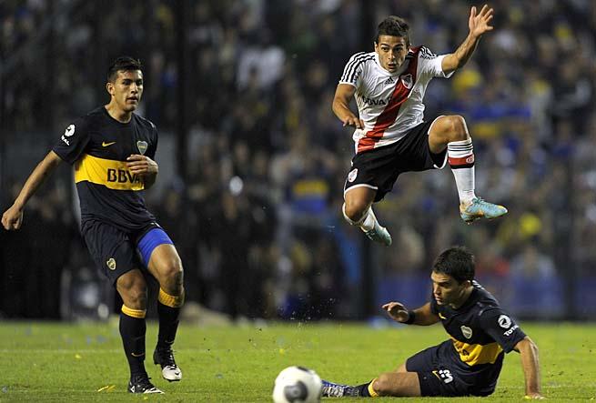 River Plate's Manuel Lanzini jumps over Boca Juniors' Matias Caruzzo in Sunday's 1-1 draw.
